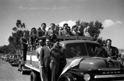 Miguel Alemán Valdés y Vicente Aguirre a bordo de camión de carga durante desfile