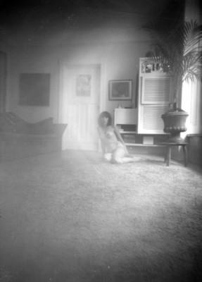 Mujer sentada desnuda al interior de una casa