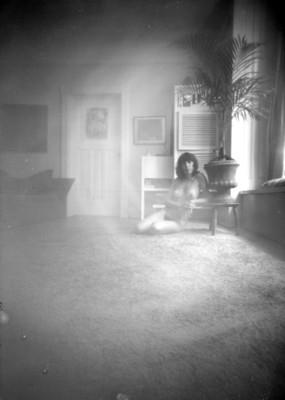 Desnudo de mujer sentada junto a una maceta