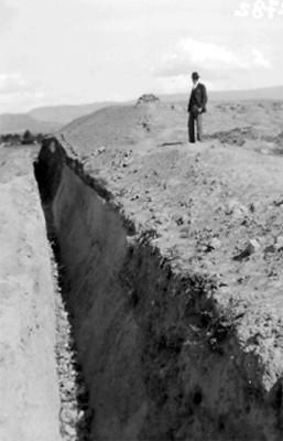 Arqueólogo sobre los restos de una construcción prehispánica