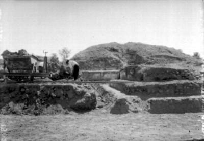 Trabajador con pico excava junto a montículo en Teotihuacán