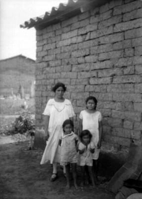 Mujer y sus tres hijos junto a un muro de adobe, retrato