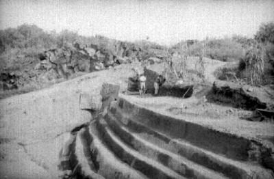 Hombres excavan edificio escalonado, vista general