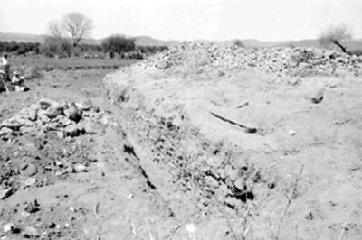Trabajadores junto a excavación de un muro prehispánico