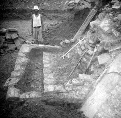 Hombre parado junto a edificio A en excavación