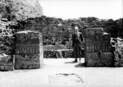 Hombre junto a fragmentos de columnas y los relieves del interior de la Pirámide del Tepozteco
