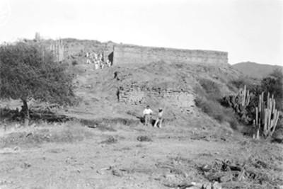 Hombres frente a una estructura arqueológica en Quiotepec