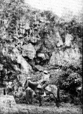 Hombres a un costado de cerro con restos de pintura rupestre