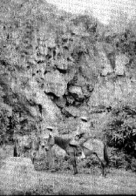 Hombres junto a un cerro con restos de pintura rupestre