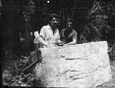 Hombres posan junto a estela en Yaxchilán