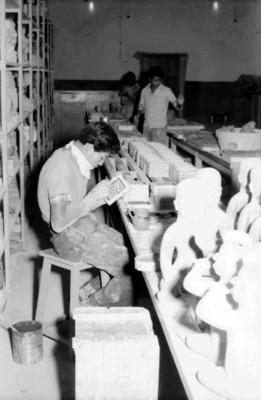 Hombre trabaja en la reproducción de una pieza prehispánica, interior de taller