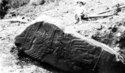 Niño frente a estela in situ, con relieves escultóricos