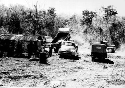 Trabajadores y camiones de cargo en el sitio arqueológico de Edzná, reprografía