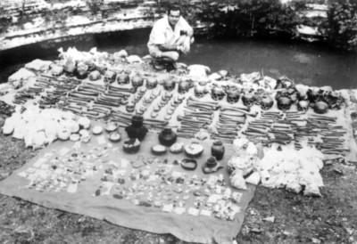 Hombre frente a lote de objetos y restos humanos hallados en el cenote sagrado de Chichén Itzá, reprografía