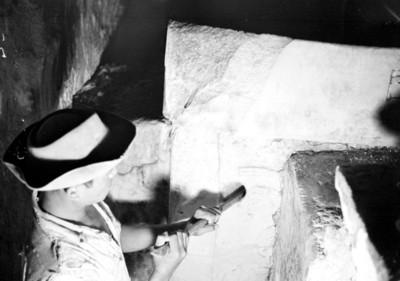 Hombre con cinsel restaura una lápida en la tumba de Pakal