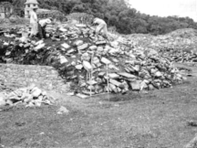 Hombres sobre la estructura del Juego de Pelota durante su reconstrucción, al fondo el Palacio