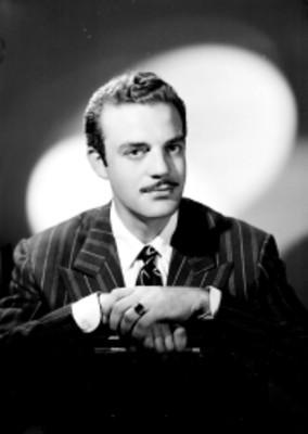 Eduardo Fajardo, actor, porta saco a rayas, recargado sobre una silla, retrato