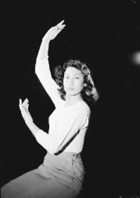 Alma Rosa Martínez, bailarina, con los brazos hacia arriba, retrato