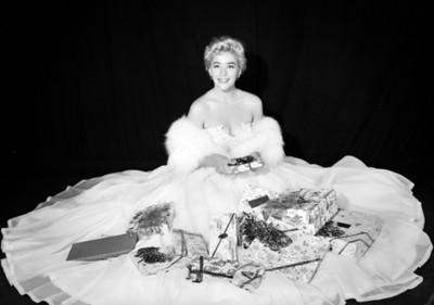 Silvia Pinal, actriz, sentada en el piso con regalos, retrato