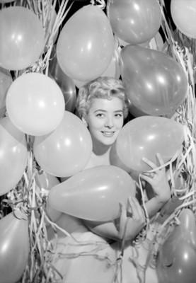Silvia Pinal, actriz, rodeada de globos y serpentinas, retrato