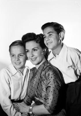Marga López acompañada de sus hijos Carlos Amador y Manuel, sonríen, retrato