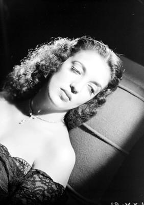 Katy Jurado, actriz, recostada sobre un sillón, retrato