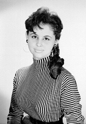 Pilar Orraca, actriz, porta blusa a rayas y de cuello alto, retrato
