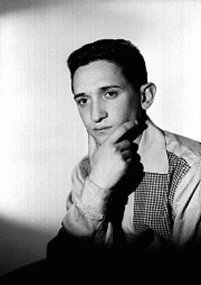 Abraham Stavans, actor, con playera estampada en frente se toma la barbilla con una mano, retrato