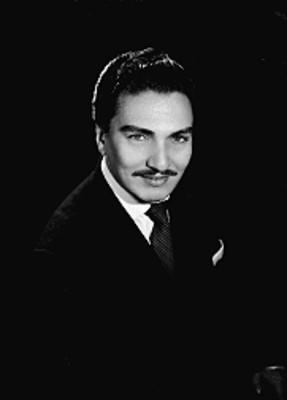 Daniel de la Vega, cantante, porta saco con corbata a rayas, sonríe, retrato
