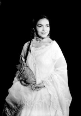 Nicte-Ha sentada en con manos y abanico en su regazo, viste traje folklorico, retrato