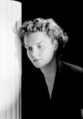 Dally Deady, actriz, viste blusa de cuello en V junto a una columna, retrato