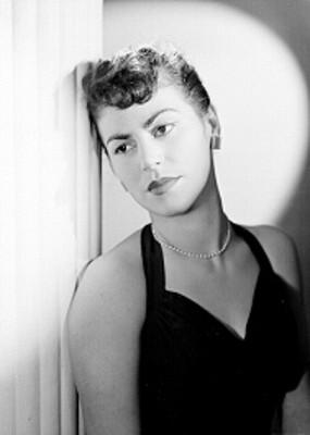 Ma. Antonieta Dominguez, actriz, recargada en una columna porta vestido halter y accesorios, retrato