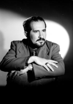 Sr. Gonzalez Contreras, escritor, sentado en una silla viste traje y corbata con los brazos cruzados, retrato