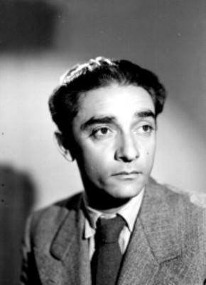 Julio Castellanos, pintor, viste de traje y corbata, retrato