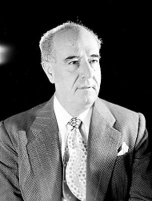 Jose Calderon, productor de cine, viste de traje a rayas y corbata decorada, retrato