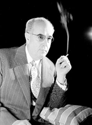 Jose Calderon, productor de cine, viste de traje y corbata con cigarrillo encendido en mano izquierda, usa anteojos, retrato