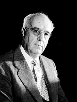 Jose Calderon, productor de cine, viste de traje y corbata, usa anteojos, retrato