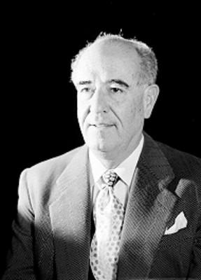 Jose Calderon, productor de cine, viste de traje y corbata, sonríe, retrato
