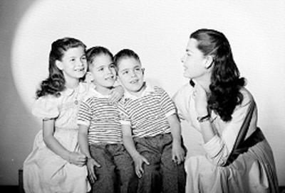 Rebeca Iturbide e hijos, sentados en una banca de madera, sonríe, retrato de grupo