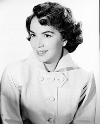 Hilda Salazar, actriz, viste abrigo de botones, sonríe, retrato