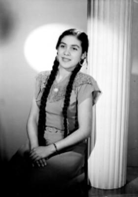 Aurora Zermeña, sentada se apoya en una columna, tiene manos en el regazo, retrato