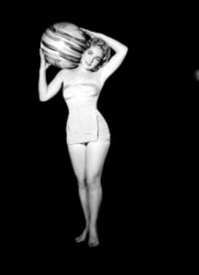 Eva Fischer, de frente, carga sobre su hombro pelota playera, viste traje de baño, retrato