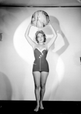 Eva Fischer, de frente eleva pelota sobre su cabeza, viste traje de baño, retrato