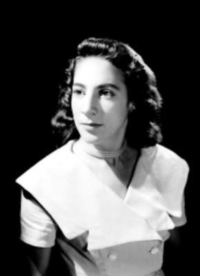 María del Carmen Flores, en tres cuartos de perfil resaltada con luz y fondo oscuro, retrato