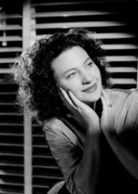 Christiane Beuque, actríz, con manos a las mejillas y codos sobre un cojín, retrato