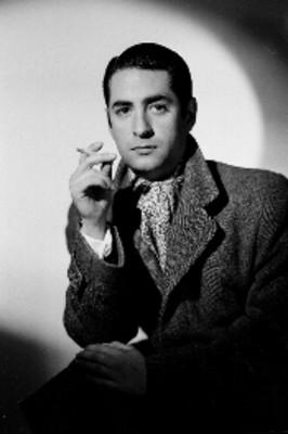 Luis Beristáin, actor, con cigarrillo en mano, viste abrigo con mascada en el cuello, retrato