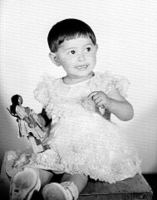 Hija de Rosa de Castilla, sentada de frente con muñeca de trapo en la mano, retrato