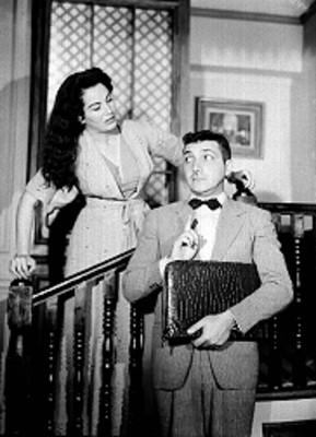 Mujer en escalera observa a un hombre con portafolio en mano debajo de ella, actores en escena