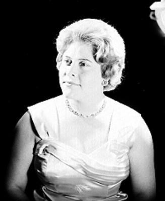 Carmen Solis, cantante de opera, porta vestido de tirantes anchos con pliegues en el pecho y accesorio, retrato de perfil