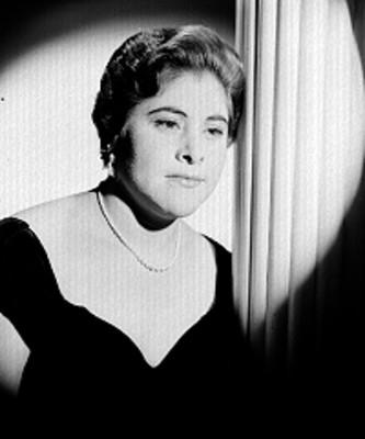 Carmen Solis, cantante de opera, recargada en una columna, porta vestido escote a los hombros y accesorios, retrato